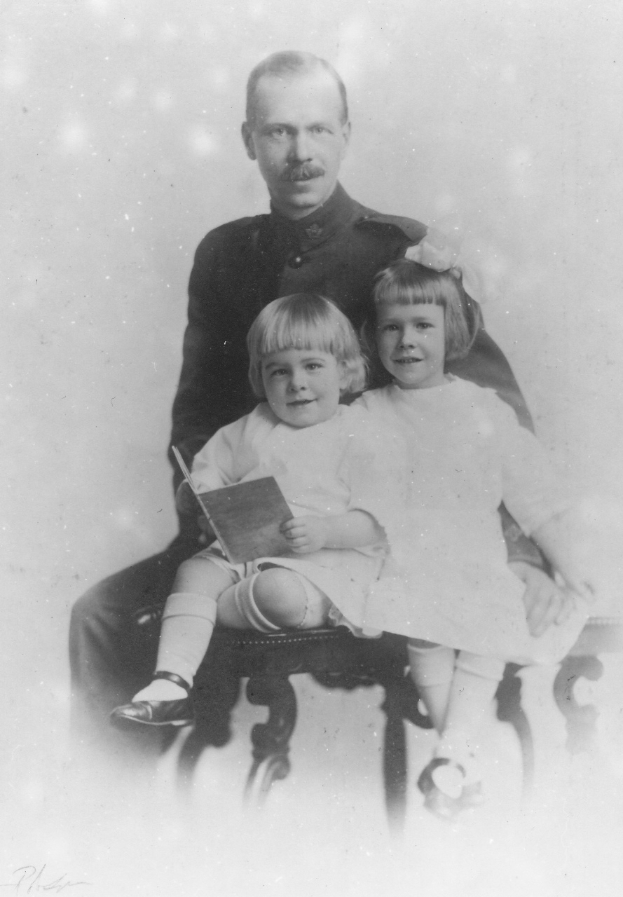 Black and white portrait of Sydney Wilcox with his two young daughters sitting on his lap.