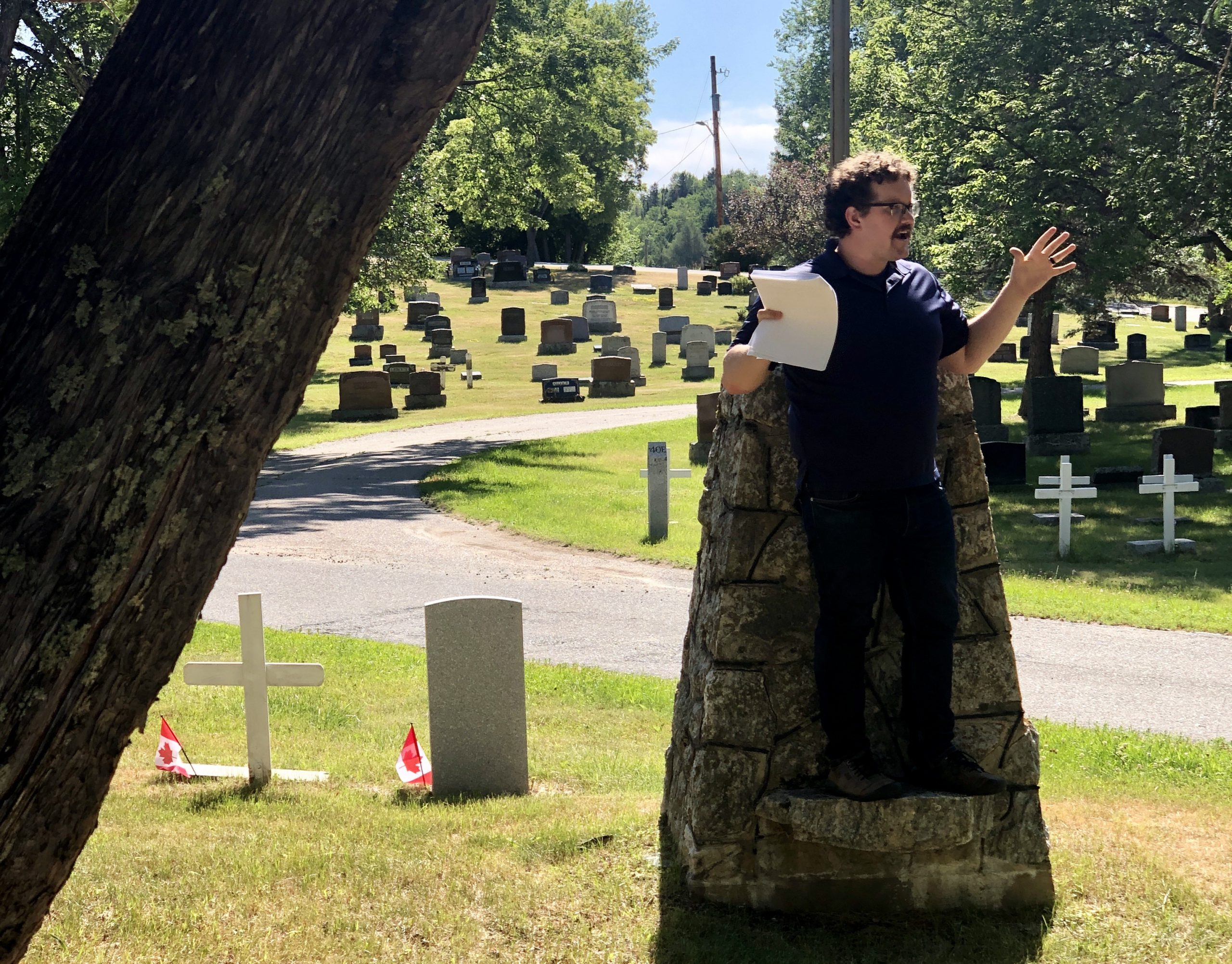 Photograph of Braden Murray, Museum Educator for the Lake of the Woods Museum, standing in the Lake of the Woods Cemetery giving a tour with animated arms in the air.
