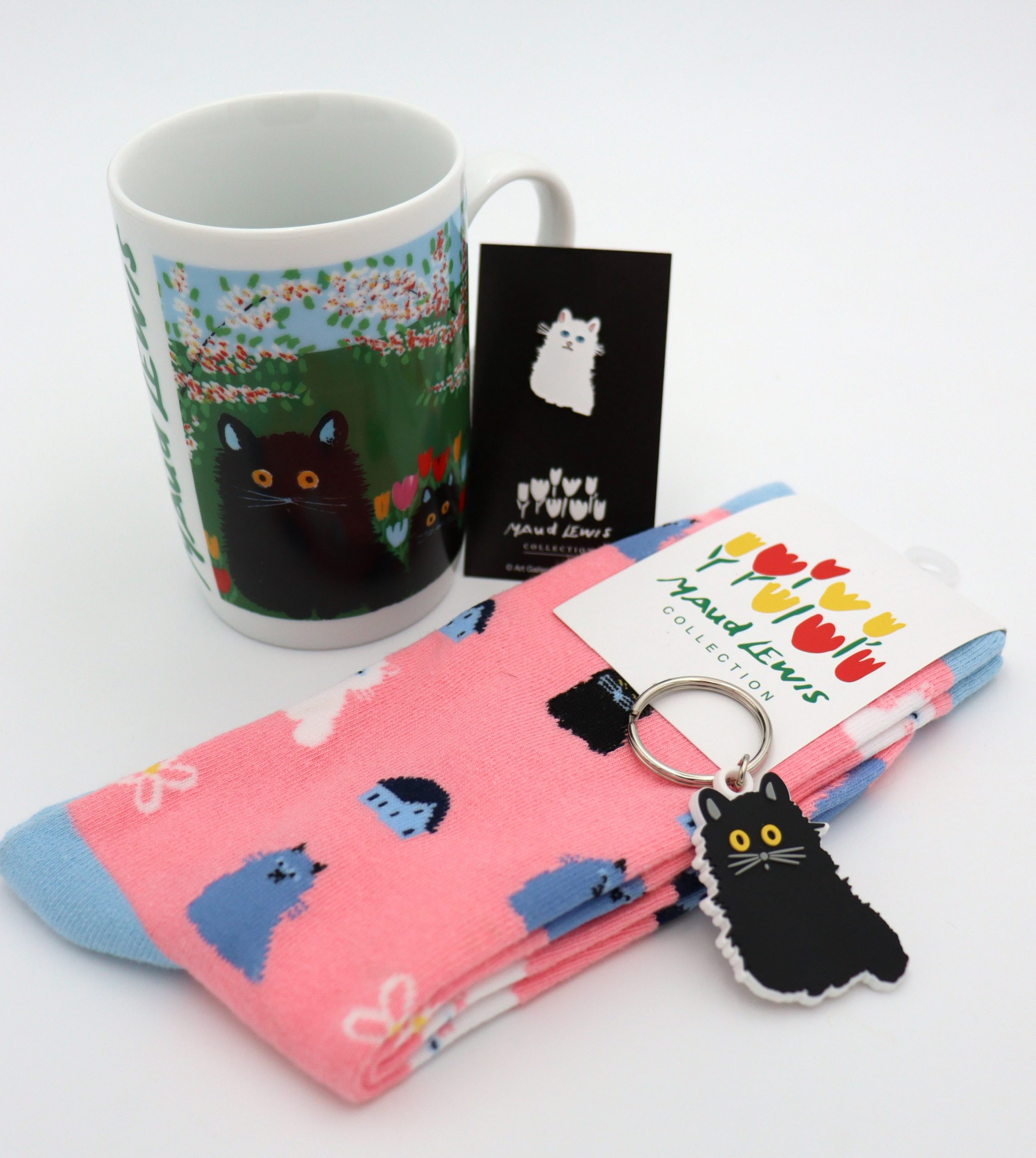 Photograph of Maud Lewis merchandise that features cats including: a mug, a white cat enamel pin, pink sucks with blue and white cats, and a black cat keychain.
