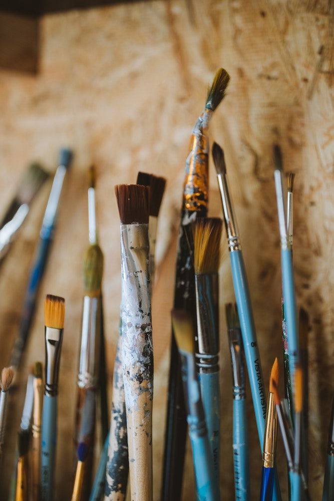 a number of artists paint brushes against a plywood background