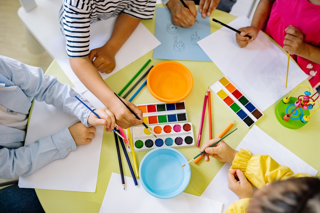 arial view of five kids painting watercolours